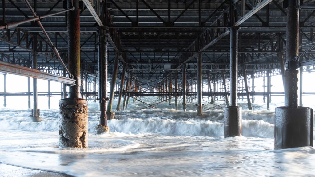 waves under a pier - photograph taken with a zoom lens with VR on (prime vs zoom lenses)